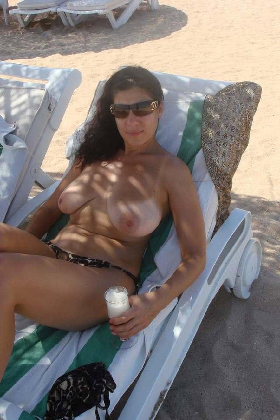 Femme mure topless à la plage